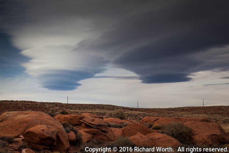 Lenticular clouds hover over the red rocks and scrub of Arizona's high desert.
