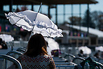 November 6, 2020: An attendee uses an umbrella to find refuge from the sun at Keeneland Racetrack in Lexington, Kentucky, on Friday, November 6, 2020. Scott Serio/Eclipse Sportswire/Breeders Cup/CSM