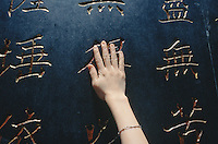 China. Province of Zhejiang. Hangzhou. Lingyin Si Temple. Temple of the Soul's Retreat. Buddhism. A woman lays her hand on the depositaries of buddhist texts. Chinese writing.  © 2004 Didier Ruef