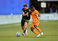 LAKE BUENA VISTA, FL - JULY 18: Pablo Bonilla #28 of the Portland Timbers is pressured by from Darwin Quintero during a game between Houston Dynamo and Portland Timbers at ESPN Wide World of Sports on July 18, 2020 in Lake Buena Vista, Florida.
