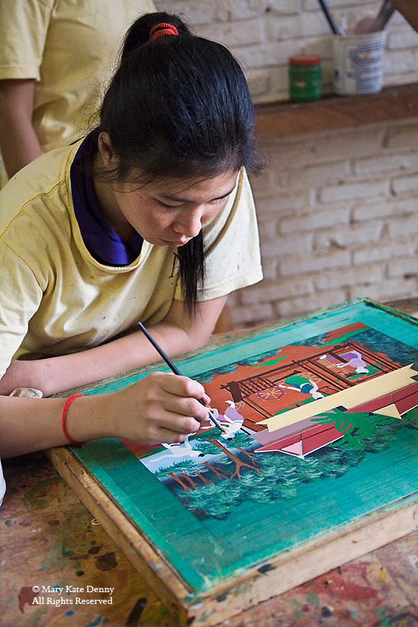 Cambodian female 20+ sits at desk and paints scene on silk in frame in handicraft.workshop in Siem Reap, Cambodia
