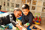 Education preschool 3-4 year olds two boys playing with human figure and wooden blocks, talking horizontal