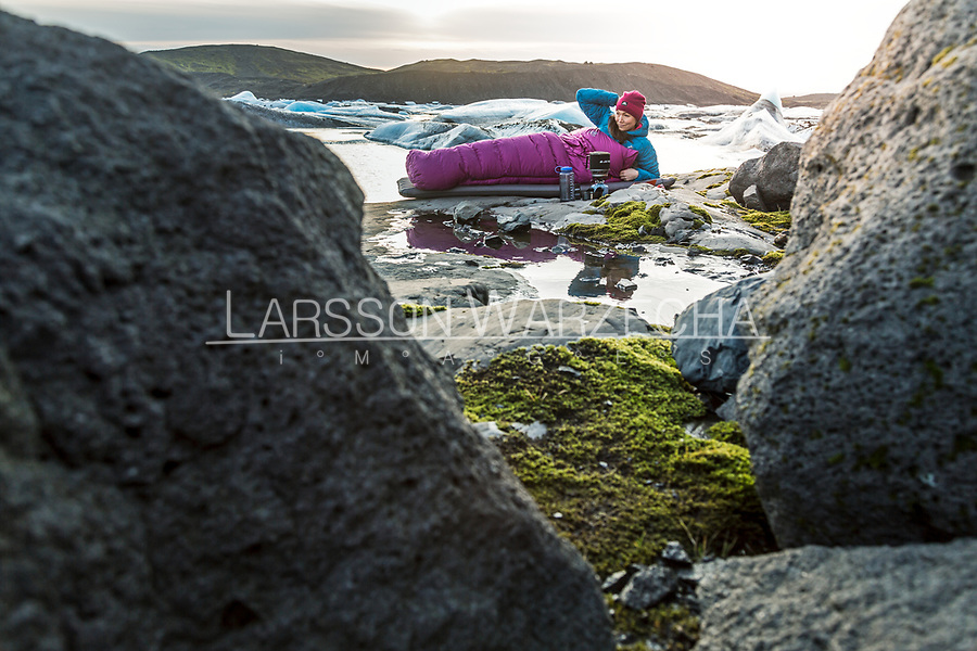 Female hiker wild camping beside a glacier, Iceland