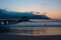 Surfing,swimming and hanging out on the pier at Hanalei Beach Park on the North Shore of Kauai, with a golden-glow sunset lighting up the water's edge and the sky over Na Pali.