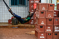 BURKINA FASO, Province Poni, Gaoua, beer pub, Brakina beer boxes, man in hammock