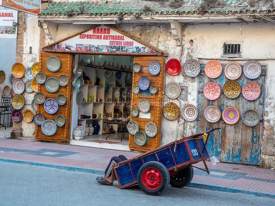 Essaouira, Morocco.  Porter Resting in his Cart in front of Ceramics Shop, Avenue de l'Istiqlal.