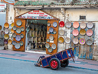Essaouira, Morocco.  Porter Resting in his Cart in front of Ceramics Shop, Avenue de l'Istiqlal.