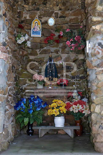Fazenda Bauplatz, Brazil. Shrine to the Black Madonna with floral tributes.