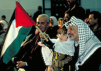 TITLE - DISTANT RELATIONS, YASIR ARAFAT HOLDS A YOUNG GIRL AT A GAZA RALLY, P.L.O., CELEBRITY. YASIR, ARAFAT. GAZA.