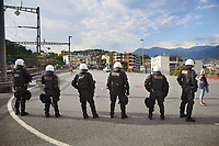 Switzerland. Canton Ticino. Lugano. Railway station. A group of police officers from TPO (Transport Police). The Policemen and a policewoman wear the special riot police black uniforms and helmets. They stand outside the railway station and look the FC Luzern football club's supporters leaving on foot the station. TPO (Transport Police) is the Swiss Federal Railways Police. Swiss Federal Railways (German: Schweizerische Bundesbahnen (SBB), French: Chemins de fer fédéraux suisses (CFF), Italian: Ferrovie federali svizzere (FFS)) is the national railway company of Switzerland. It is usually referred to by the initials of its German, French and Italian names, as SBB CFF FFS. 2.06.2017 © 2017 Didier Ruef