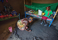 AWright_SUD_002393.jpg<br /> South Sudan<br /> Monica Yangi (right) is a BRAC student at a school in Juba. Her sister, Lillien, cleans the floor with mud as they talk.