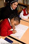 Parochial School Bronx New York  Kindergarten nun in habit working with child vertical