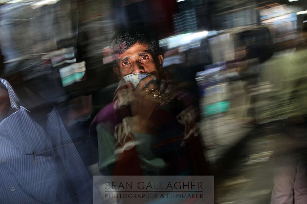 In downtown Kolkata, a man covers his face from the intense air pollution which plagues the city. It is believed that upwards of 70 percent of people in the city suffer from some form of respiratory problem as a result of the city's air.  India. November, 2013