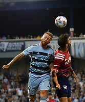 KANSAS CITY, KS - JULY 31: Johnny Russell #7 of Sporting Kansas City and Ryan Hollingshead #12 of FC Dallas go up for a header during a game between FC Dallas and Sporting Kansas City at Children's Mercy Park on July 31, 2021 in Kansas City, Kansas.