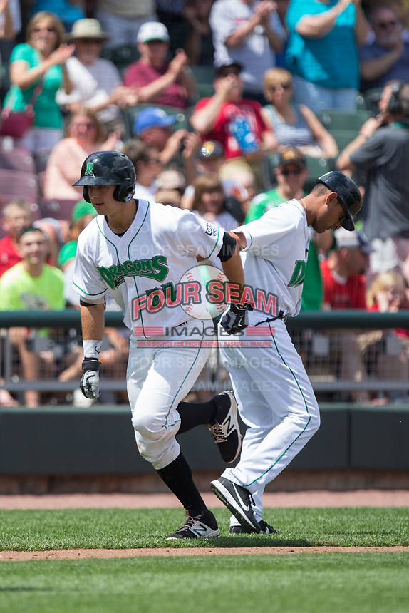 Bruce Yari (24) of the Dayton Dragons is congratulated by third base coach/manager Luis Bolivar (14) as he rounds the bases after hitting a home run against the West Michigan Whitecaps at Fifth Third Field on May 29, 2017 in Dayton, Ohio.  The Dragons defeated the Whitecaps 4-2.  (Brian Westerholt/Four Seam Images)