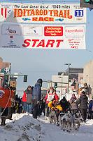 Musher Jodi Bailey and Iditarider  Dan Faltyn.leave the 2011 Iditarod ceremonial start line in downtown Anchorage, Alaska