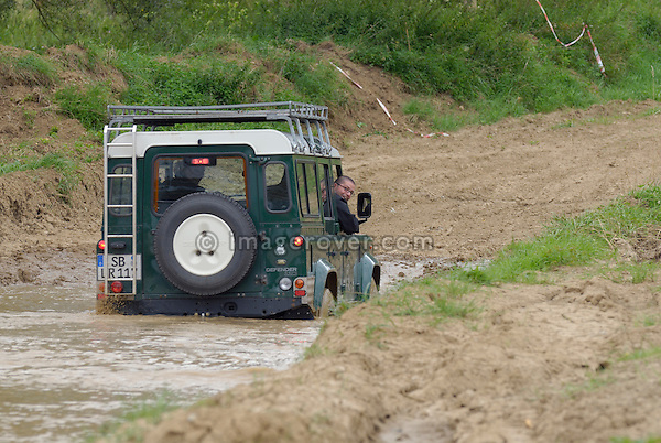 Land Rover driving off road through a flooded dirt road in Bining, France. --- No releases available. Automotive trademarks are the property of the trademark holder, authorization may be needed for some uses.