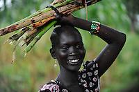 SOUTH SUDAN  Bahr al Ghazal region , Lakes State, town Rumbek , portrait of Dinka woman, carrying sugarcane