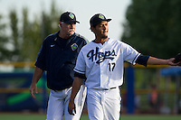 Hillsboro Hops pitcher Carlos Hernandez (17) walks from the bullpen to the dugout with pitching coach Doub Drabek (15) prior to a game against Tri-City Dust Devils at Ron Tonkin Field in Hillsboro, Oregon on August 24, 2015.  Tri-City defeated Hillsboro 5-1. (Ronnie Allen/Four Seam Images)