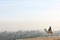 A policeman on an camel overlooking the skyline of Cairo, Egypt