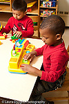 Education preschool 3-4 year olds two boys sitting at table playing separately with different toys vertical