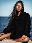 Beautiful young woman with long dark hair wearing a black sweater sitting on sand at the beach Image © MaximImages, License at https://www.maximimages.com
