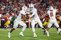 LOS ANGELES, CA - SEPTEMBER 11: Tanner McKee #18 hands off to Austin Jones #20 of the Stanford Cardinal during a game between University of Southern California and Stanford Football at Los Angeles Memorial Coliseum on September 11, 2021 in Los Angeles, California.