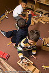 Education preschoool children ages 3-5 block area group of three boys playing  one boy showing another a toy and talking to him vertical