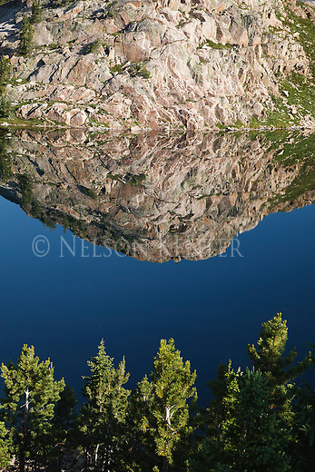 Reflections of a rocky mountain in a small  lake in the beartooth wilderness in montana