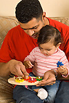 Father showing 10 month old baby girl how a wooden gear toy works