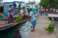 Men removing bunches of bananas from a traditional dhoni boat, Maldives.