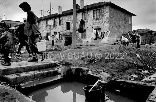 Gradisht, Albania<br /> February 1997<br /> <br /> People who have moved from the poor conditions of the north into housing originally built for political internment. There is only running water outside. All of the residents lost money on the pyramid schemes.