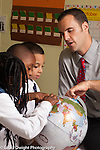 Education Elementary School male teacher working with small group looking at globe together