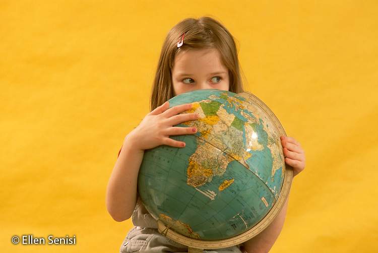 MR / Schenectady, NY. Yates Arts in Education Magnet Elementary School. Grade 2. Portrait of student (girl, 6) partially hiding behind earth globe. MR: Koe2. ID: AJ-LC. © Ellen B. Senisi
