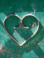 Detail of a heart on rusting green painted metal