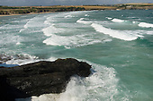 Waves break against rocks close to the village of Trevone in North Cornwall.