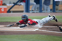 Freddy Zamora (23) of the Carolina Mudcats slides head first across home plate during the game against the Kannapolis Cannon Ballers at Atrium Health Ballpark on June 10, 2021 in Kannapolis, North Carolina. (Brian Westerholt/Four Seam Images)