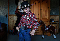 "Dressed as a cowboy Sheriff, Tanner Lauman takes a stance to not be reckoned with.<br /> <br /> Kitty Lauman trains mustangs--as she says working with the horses, not against them.  They have a ranch in Prineville, OR.<br /> <br /> Kitty, her husband Rick and their children, Josie, 2 ½,  and Tanner, 5,  ride mustangs. Kitty Lauman started her career as a horse trainer at the tender age of nine, under the guidance of her grandfather, John Sharp. <br /> <br /> She later became a top Pee Wee and High School Rodeo contestant, competing in barrel racing and cutting, among other events. Despite her mother's assertion that ""horse training isn't a real job,"" Kitty managed to make a living as a trainer after high school (and her mom now helps out with the business!) <br /> <br /> Kitty won the title of Miss Rodeo Oregon in 1994, and since then, has continued to expand her horse training knowledge and experience.  She placed second in the Extreme Mustang Makeover, a national competition in 2008."
