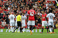 Pictured: Jordi Amat argues with match referee Mike Dean. Saturday 16 August 2014<br />