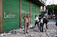 Anti-government protesters working tirelessly to break up paving stones to hurl at pro-Mubarak supporters in Tahrir Square. Continued anti-government protests take place in Cairo calling for President Mubarak to stand down. After dissolving the government, Mubarak still refuses to step down from power.