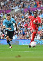 July 26, 2012..UAE's Abdulaziz Hussain (3) and Uruguay's Jonathan Urretaviscaya (120 in action. UAE vs Uruguay Football match during 2012 Olympic Games at Old Trafford in Manchester, England. Uruguay defeat United Arab Emirates 2-1...