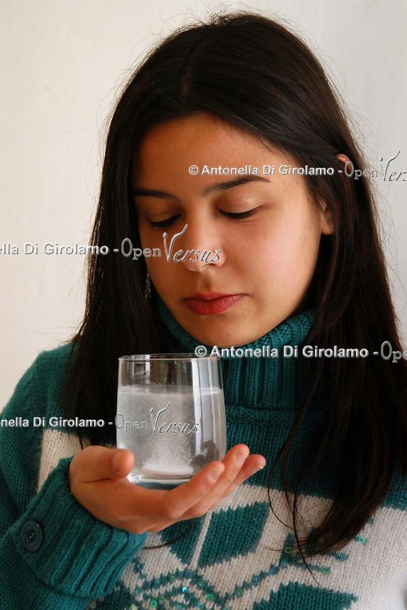 Ragazza prende aspirina contro influenza. Girl takes aspirin against flu....