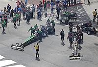 Apr. 7, 2013; Las Vegas, NV, USA: NHRA crew members push in the next pair of top fuel dragster drivers Khalid Albalooshi (near lane) alongside Terry McMillen during the Summitracing.com Nationals at the Strip at Las Vegas Motor Speedway. Mandatory Credit: Mark J. Rebilas-