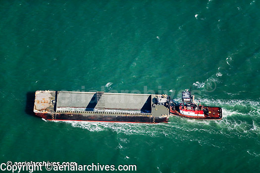 aerial photograph of a tug boat pushing an empty barge in San Francisco bay