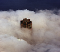 aerial photograph 555 California Street tower piercing through the fog, San Francisco, California