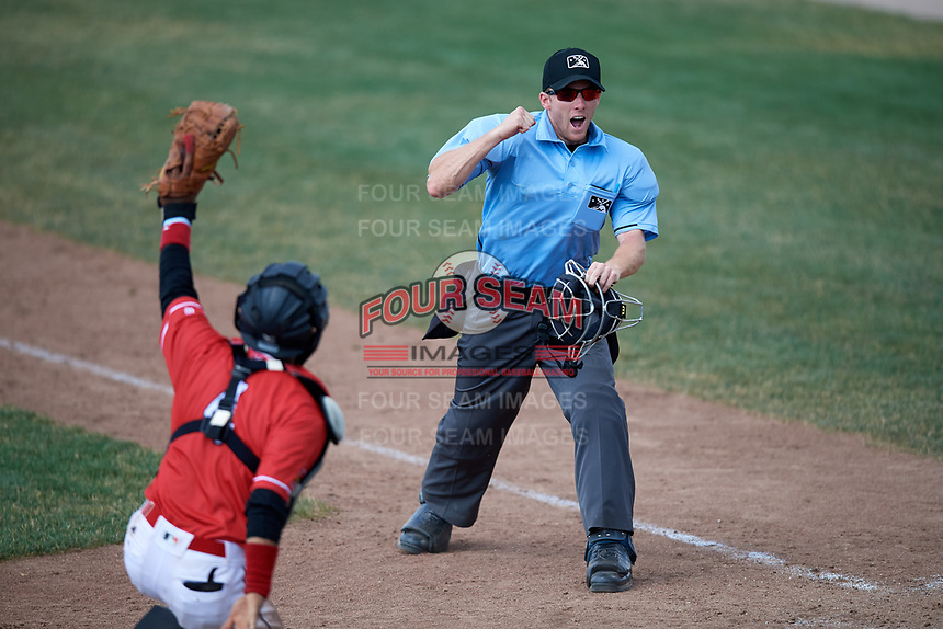 Umpire Dylan Bradley calls Korby Batesole (not shown) out at home as catcher Pablo Garcia (4) shows the ball in his glove during a game between the Lowell Spinners and Batavia Muckdogs on July 15, 2018 at Dwyer Stadium in Batavia, New York.  Lowell defeated Batavia 6-2.  (Mike Janes/Four Seam Images)