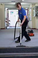 Cleaner vacuuming the corridors,  State Secondary Roman Catholic school.