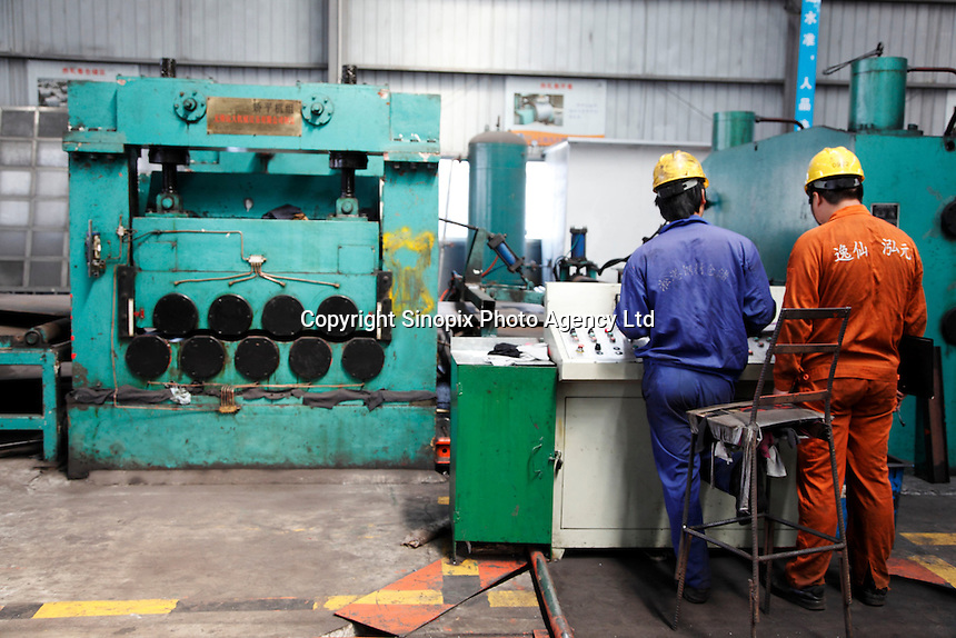 A worker operates a machine that flattens steel plates at a steel stockyard run by the Shanghai Yirong Trading Company Ltd in Shanghai, China..10 Apr 2009