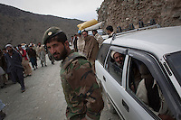 An ANA (Afghan National Army) soldier helps secure the site of a roadside bomb explosion near Naray villager in Kunar. The bomb destroyed a supply truck carrying Humvee spare parts.
