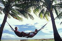 Couple in hammock framed by palm trees, Kauai, Hawaii